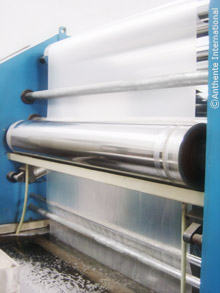Extrusion machine stretching the polypropylene into a thin fabric.