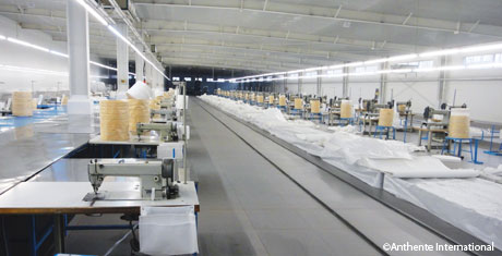 Interior view of the new factory in Shandong, China with a bank of new industrial sewing machines.